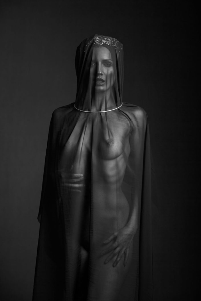 Nude fashion portrait of girl in a black shroud safety pin crown and metal collar fashion photographer Melbourne